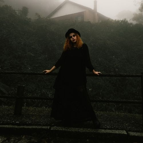 Black female goth poses in black alternative clothing in a foggy setting
