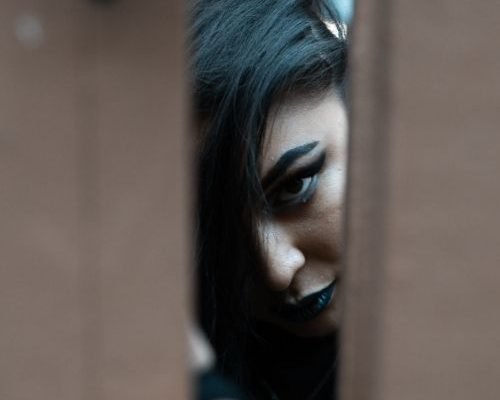 Woman wearing gothic makeup including black lipstick and winged eyeliner looks through a gap