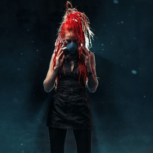 white woman with bright red hair poses with a mask