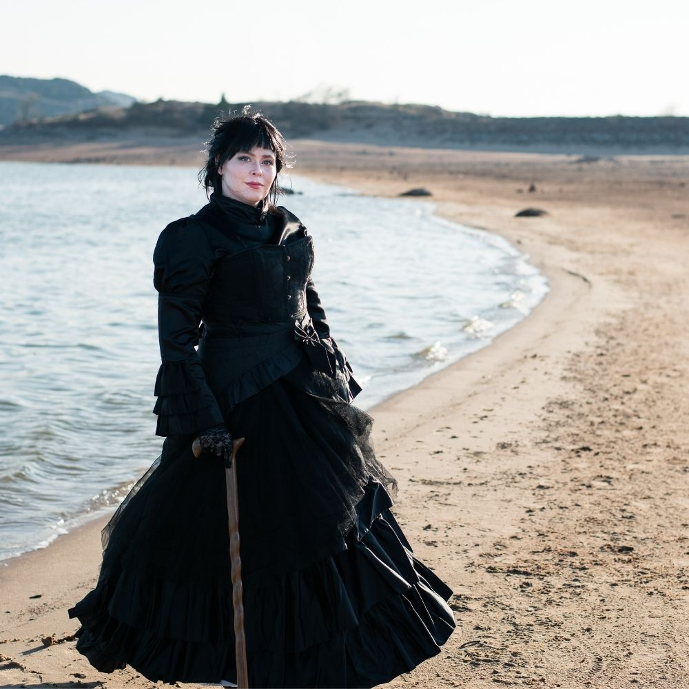A woman wearing victorian mourning attire on a beach